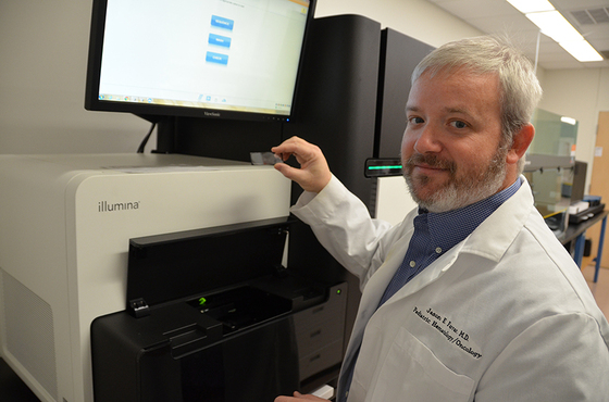 Jason Farrar, M.D., assistant professor in the UAMS College of Medicine Department of Pediatrics, explains the process of using a HiSeq 3000 system to sequence DNA and RNA molecules, such as those used in his ongoing acute myeloid leukemia research.