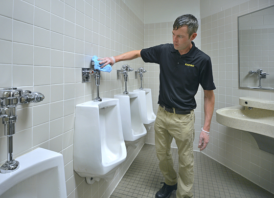 Cleaning a urinal touchpoint with a microfiber SmartTowel in a restroom.