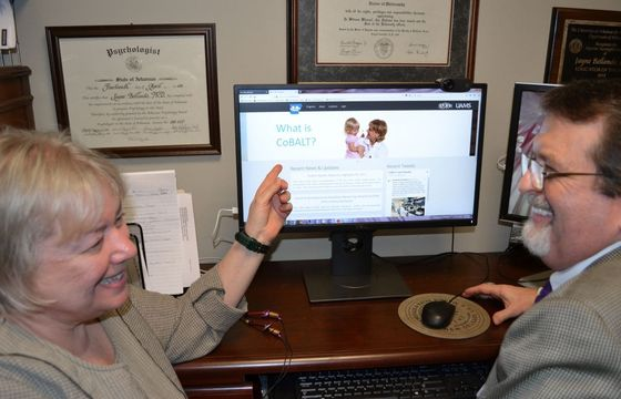 Jayne Bellando, Ph.D., shows Timothy Thomas, M.Ed., the new CoBALT website, which gathers resources about autism and other developmental disorders into a one-stop shop for both families and health care providers. Ballando is co-director of CoBALT along with Eldon Schulz, M.D., and Thomas is director of the Dennis Developmental Center.