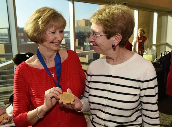 Jean C. McSweeney, Ph.D., R.N., professor, associate dean for research and co-director of the Ph.D. program in the UAMS College of Nursing, shows off the medallion from her investiture in the Women's Cardiovascular Health Professorship to Jeannette M. Shorey II, M.D., associate dean for faculty affairs in the UAMS College of Medicine and associate provost for faculty.