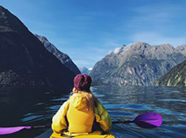 View from behind a woman wearing a yellow raincoat, who is paddling in a canoe in a lake near mountains.