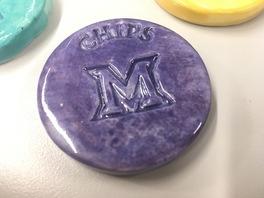 A purple ceramic chip with the Miami M