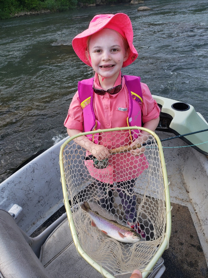 A youngster enjoys the experience of netting a trout on the Spring River. Photo by Mark Crawford