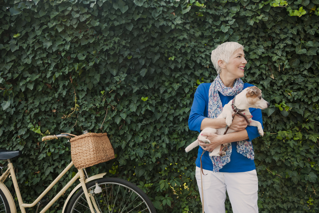 Woman with dog and bicycle enjoys her phased retirement