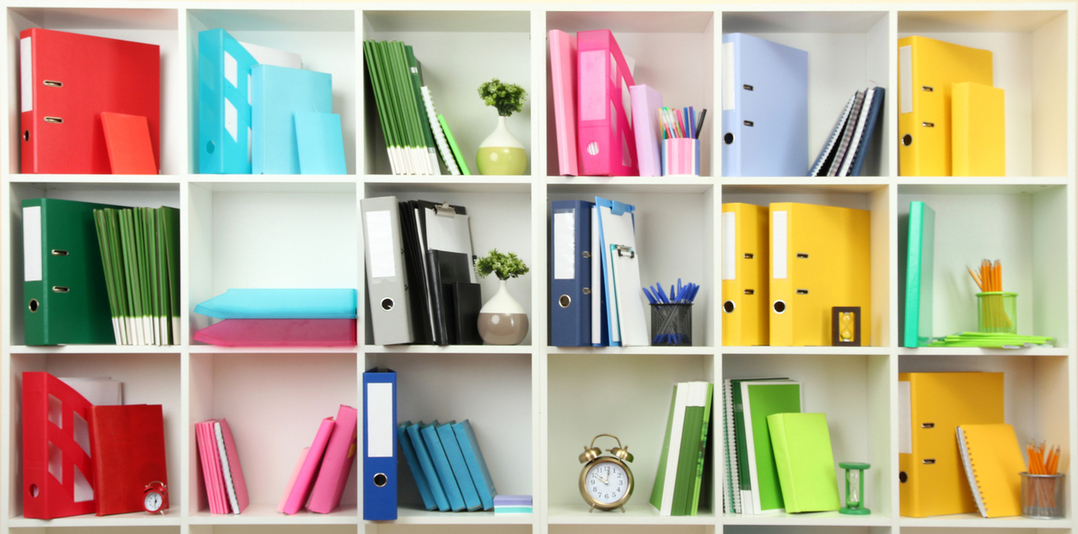 Colorful binders on a white shelf