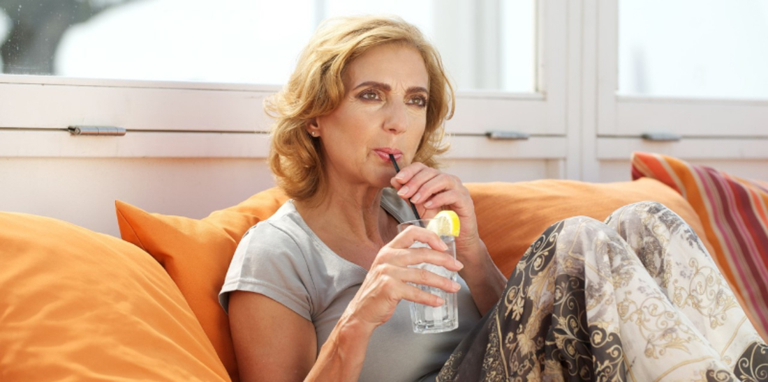 Woman drinking ice water with lemon on couch indoors