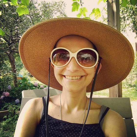 NET cancer blogger in summer garden wearing hat and sunglasses