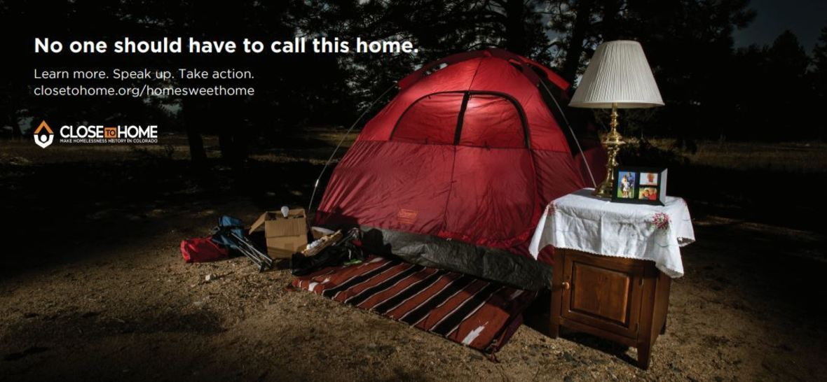 Camp site home set up with words, 'No should have to call this home.'