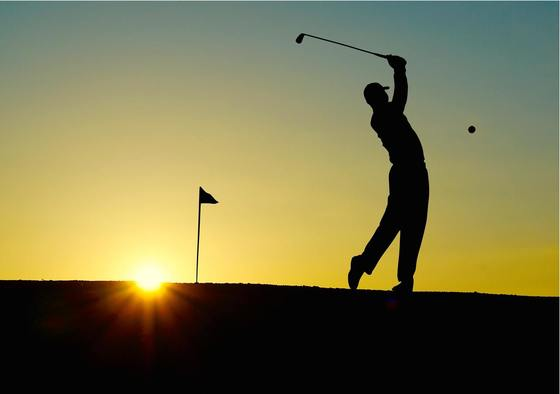 Golfer teeing off at sunrise.