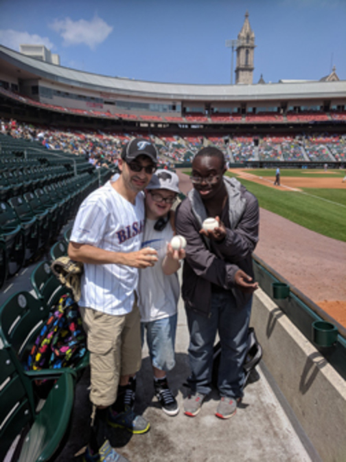 3 young men, participants in the Young Adult Life Transitions group, holding game balls at a Bisons baseball game at Coca-Cola Field