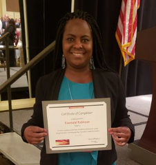 Kaamalal Robinson holding her LeadingAge New York IGNITE Leadership Academy certificate.
