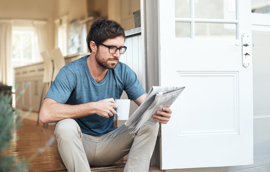 A man reads a paper and considers his options for starting over.