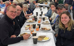 People at table eating breakfast at benefit event