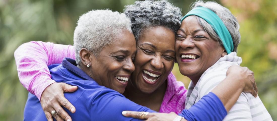 Black women in exercise clothing hugging