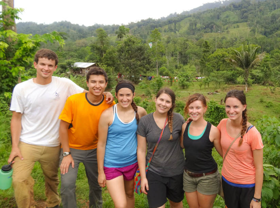 Six people in a tropical setting with a building in the background