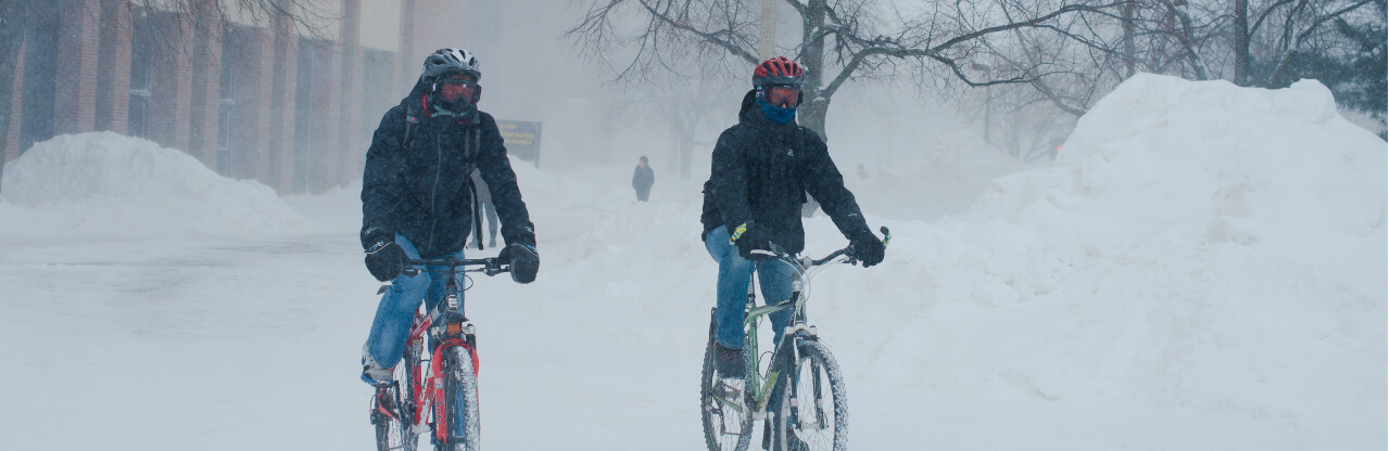 Two people riding bicycles in the snow.