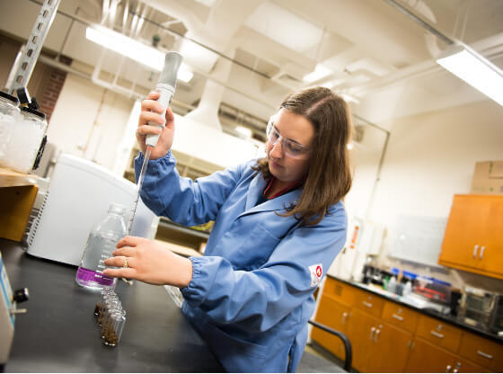 Rebecca Ong filling glass containers in a lab.