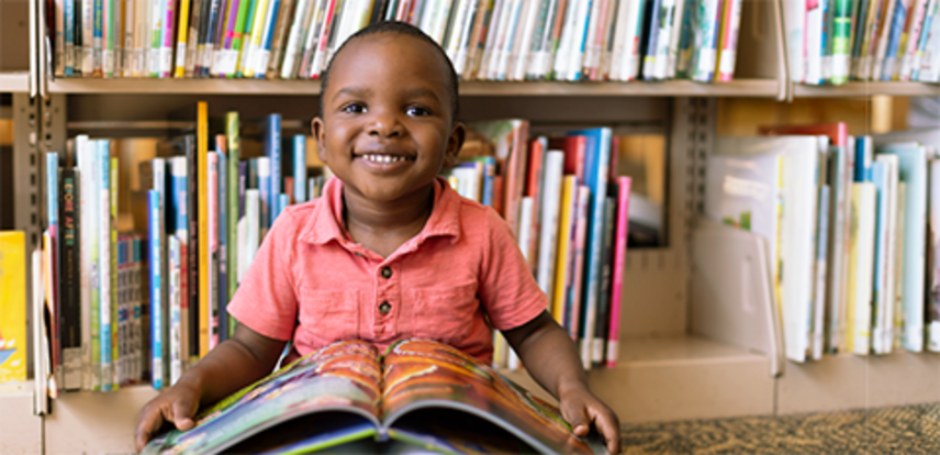 Child reading a book at the library, link to Library Foundation donation page