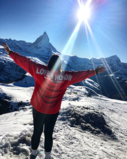 Person standing on a mountaintop with a red Love and Honor sweatshirt.