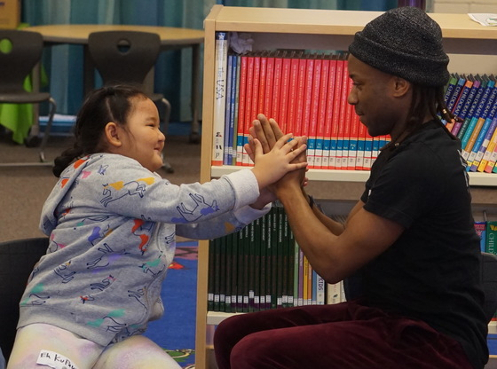 A Participant and Teaching Artist share a moment of connection during class.