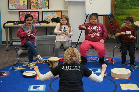 Four students play drums and shakers as part of a Rhythm Orchestra, lead by a Teaching Artist.