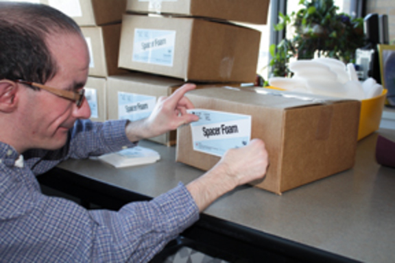 Man labeling a box in an office environment.