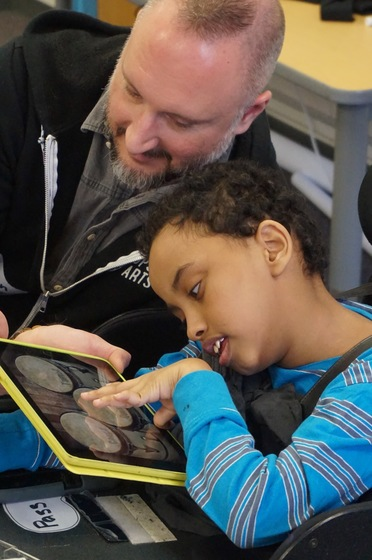 A Teaching Artist offers a student the drum app on the ipad during Rhythm Orchestra.
