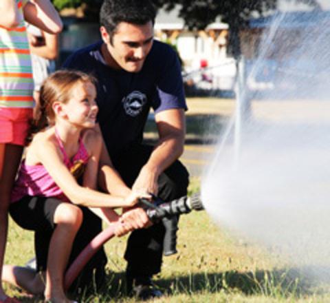 A Gresham Fire Cadet teaches a girl fire safety.