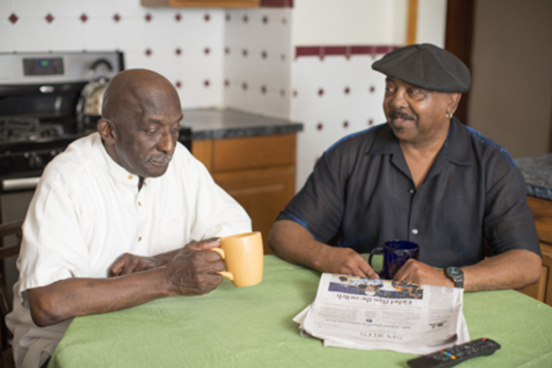 A People Inc. program participant and his companion seated at a kitchen table having coffee.