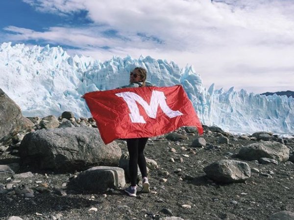 girl holding Miami flag, glaciers in background