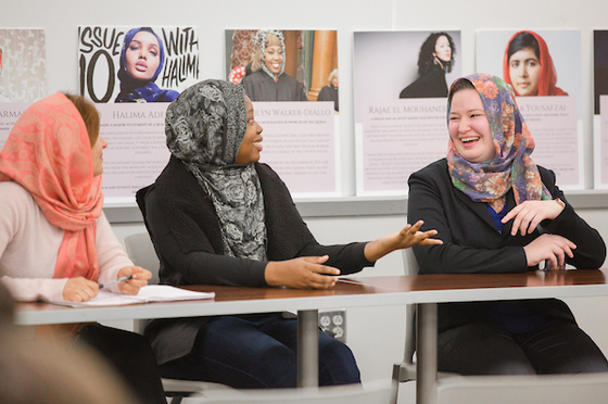 three women with hijabs on, talking with eachother, smiles and laughs