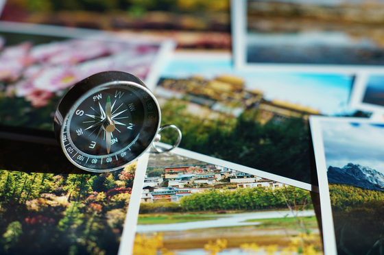 collage of travel images, compass sitting on top of the photos