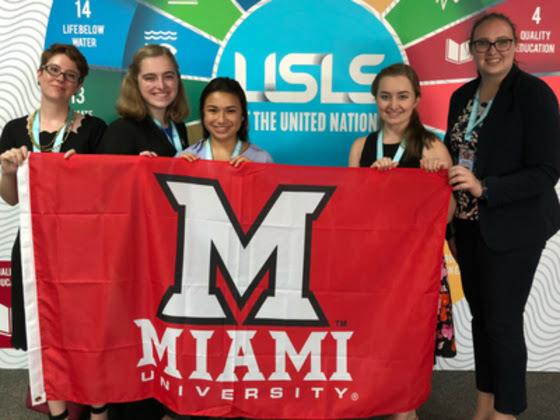 5 Miami students holding the Miami flag at a past United Nations conference