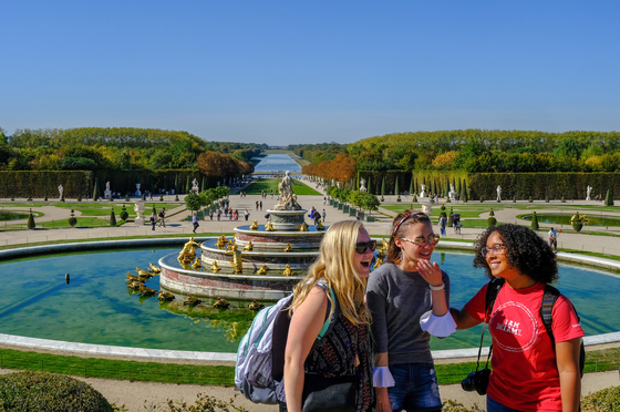 Three Miami students studying abroad posing and laughing in front of the fountain outside of Versailles. One student has a red Miami t-shirt on.