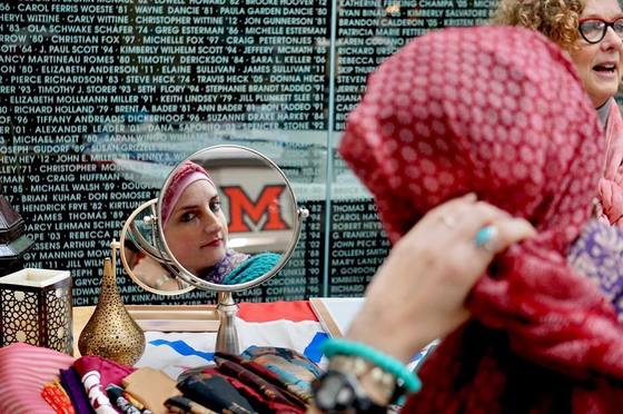 woman putting hijab on and looking into a mirror that has the Miami logo reflecting in it