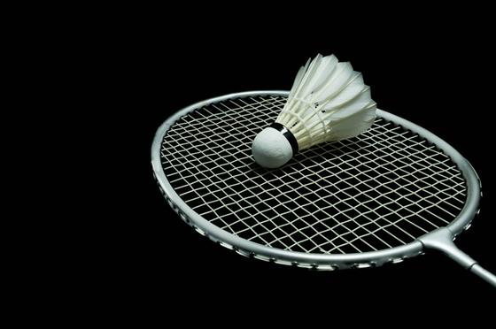 badminton racket and birdie, black background