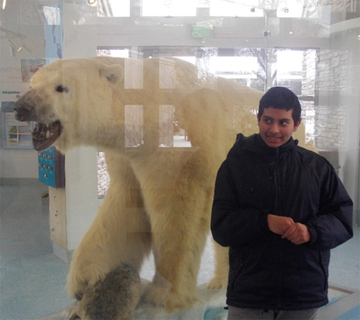 Photo of Malihur posing by the Polar Bear taxidermy mount at the Buffalo Zoo.