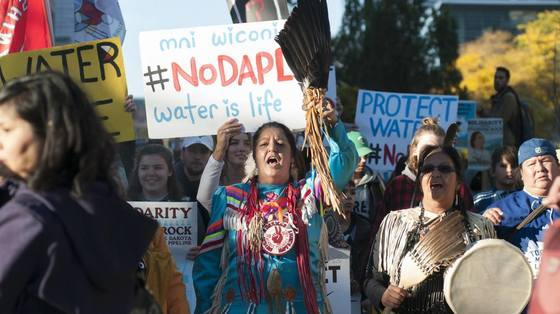 """Washington D.C. march, woman holding sign that says """"#NoDAPL water is life"""""""