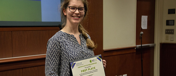 Elizabeth Perner holds her first place award from the Three Minute Thesis Competition