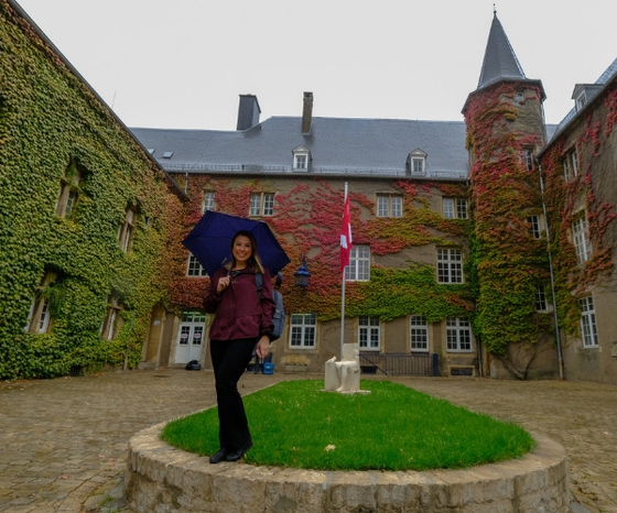 a woman stands holding an umbrella, with the Luxembourg campus building in the background