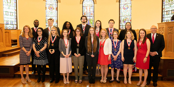 group photo of many students who won an award standing with President Crawford and Dr. Renate Crawford, all have metals around their necks