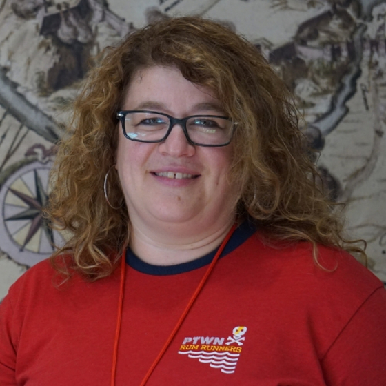 A woman with blond curly hair and glasses smiles at the camera
