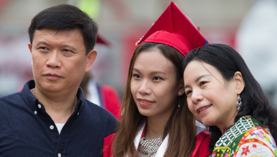 An international student wearing a graduation cap and gown poses with her parents