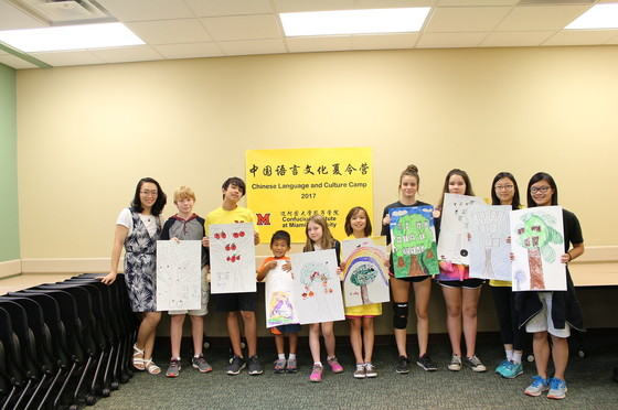 a line of children stand holding posters they created