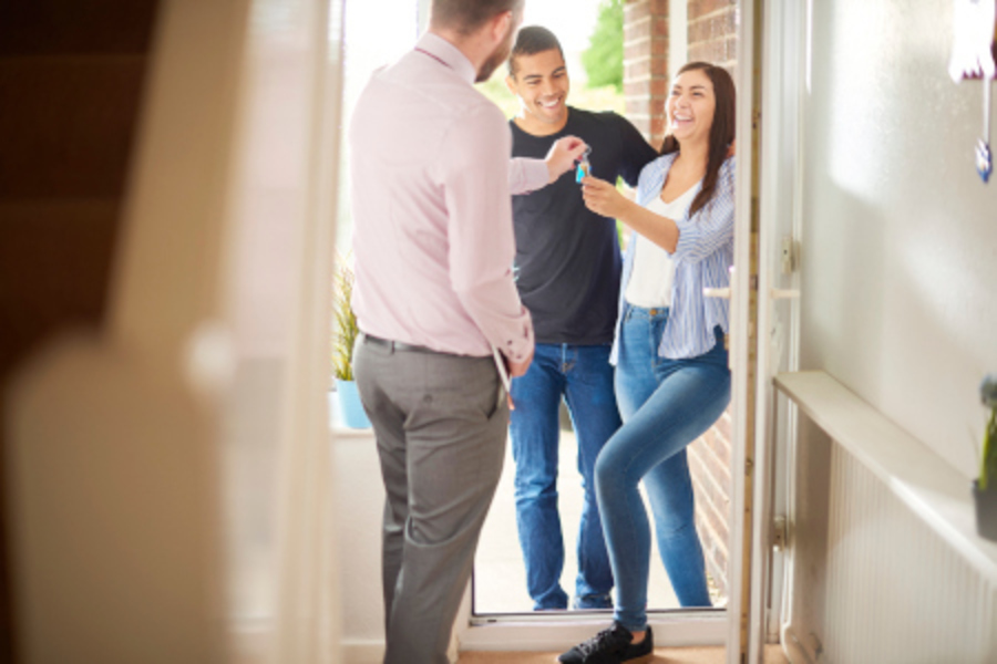 Young couple accepts keys to home.