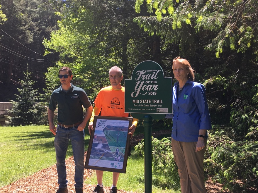 Secretary Dunn, DCNR staff and Mid State Trail staff pose next to the new Trail of the year sign