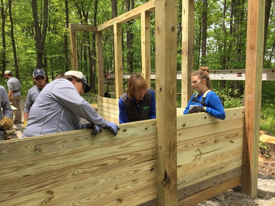 Secretary Dunn assists PA outdoor corps members as they construct shelters in the woods
