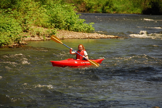 A girl in a red kayak paddles down a creek with green bushes on the rocky shoreline