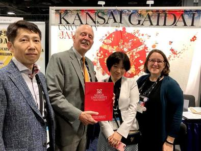 """Four people standing in front of a """"Kansai Gaidai"""" sign, smiles, holding Miami University red folder"""