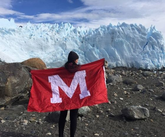 student holding Miami flag in front of a glacier